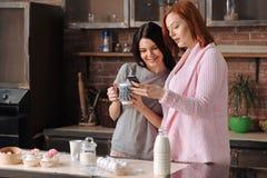 Молодые дружелюбные девушки смотря телефон Стоковая Фотография RF
