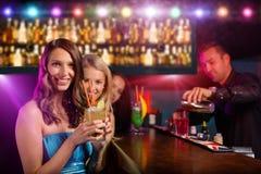 Молодые друзья выпивая коктеили совместно на партии Стоковые Фотографии RF