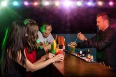 Молодые друзья выпивая коктеили совместно на партии стоковые изображения rf