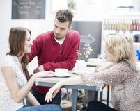 Молодые друзья имея кофе на кафе Стоковые Изображения