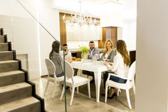 Молодые друзья имея обедающий дома и провозглашать с белым вином Стоковые Изображения