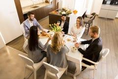 Молодые друзья имея обедающий дома и провозглашать с белым вином Стоковые Изображения RF