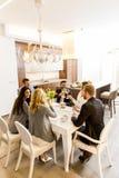 Молодые друзья имея обедающий дома и провозглашать с белым вином Стоковые Фотографии RF