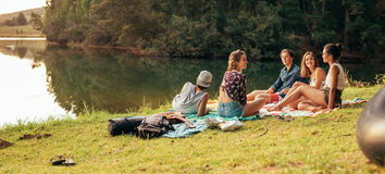 Молодые друзья наслаждаясь днем на озере Стоковые Изображения RF