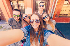 Молодые друзья смеясь над и принимая selfie стоковая фотография rf