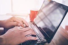 молодые руки бизнесмена используя портативный компьютер с красной кофейной чашкой Стоковые Фотографии RF