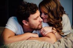 Молодые сексуальные пары в влюбленности лежа в кровати в гостинице, обнимая на белых листах, конец вверх Стоковое Фото