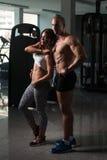 Молодые сексуальные пары фитнеса представляя в спортзале Стоковые Фото