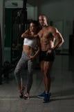 Молодые сексуальные пары фитнеса представляя в спортзале Стоковые Изображения