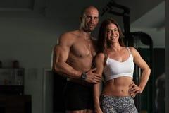 Молодые сексуальные пары фитнеса представляя в спортзале Стоковое Изображение