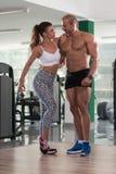 Молодые сексуальные пары фитнеса представляя в спортзале Стоковое Фото