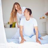Молодые смеясь над пары имея потеху в спальне дома Стоковое фото RF