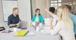 Молодые сотрудники исследуя график в офисе сток-видео