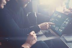 Молодые сотрудники обсуждая идеи дела на рабочем месте Рука бородатого человека poiting к дисплею компьтер-книжки Конец усаживани Стоковые Изображения