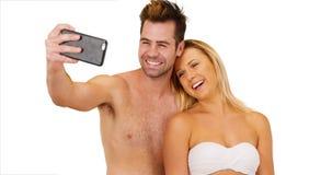 Молодые социальные средства массовой информации преследовали пар принимая selfies перед белой предпосылкой стоковое фото rf