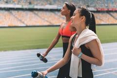 Молодые спортсменки при бутылки воды идя на идущий стадион следа Стоковая Фотография RF
