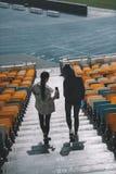 Молодые спортсменки с бутылками спорта на лестницах стадиона Стоковая Фотография RF