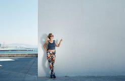 Молодые спорт и красивая белокурая девушка в sportswear показывают руку u Стоковое Фото