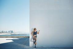 Молодые спорт и красивая белокурая девушка в sportswear показывают руку u Стоковая Фотография RF