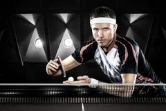 Молодые спорт укомплектовывают личным составом теннисист в игре на черноте стоковые фото