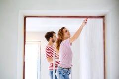 Молодые стены картины пар в их новом доме Стоковая Фотография RF
