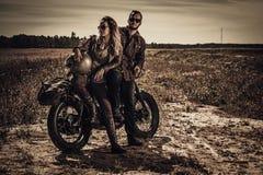 Молодые, стильные пары гонщика кафа на винтажных изготовленных на заказ мотоциклах в поле стоковые фото