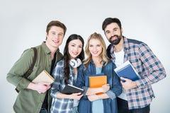 Молодые студенты в вскользь одеждах держа книги на белизне Стоковая Фотография