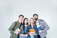 Молодые студенты в вскользь одеждах держа книги на белизне Стоковое фото RF