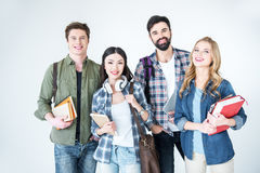 Молодые студенты в вскользь одеждах держа книги на белизне Стоковая Фотография RF