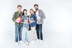Молодые студенты в вскользь одеждах держа книги на белизне Стоковые Изображения