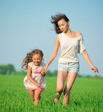 Молодые счастливые девушки бежать на зеленом пшеничном поле Стоковые Изображения RF