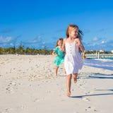 Молодые счастливые девушки имея потеху на экзотическом пляже дальше Стоковые Изображения RF