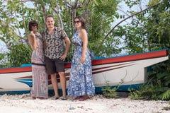 Молодые счастливые женщины и человек представляя около старого корабля на тропическом пляже с белым песком bali Индонесия Стоковое Изображение RF
