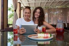 Молодые счастливые женщины наблюдая видео на сенсорной панели пока ослабляющ совместно в современном интерьере кофейни, Стоковое Фото