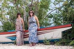 Молодые счастливые женщины представляя около старого корабля на тропическом пляже с белым песком bali Индонесия Стоковое фото RF
