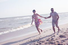 Молодые счастливые пары бежать совместно стоковая фотография rf