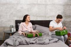 Молодые счастливые пары в пижамах распаковывая их настоящие моменты пока сидите Стоковые Фотографии RF