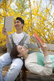 Молодые счастливые пары лежа и сидя на скамейке в парке наслаждаясь читающ их книги, outdoors в весеннем времени Стоковая Фотография
