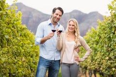 Молодые счастливые пары держа бокал вина и смотря камеру стоковое фото
