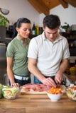 Молодые счастливые пары подготавливая обед стоковая фотография