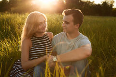 Молодые счастливые пары сидя совместно на траве держа их руки Стоковая Фотография