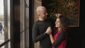 Молодые счастливые пары стоят около панорамного окна в кафе видеоматериал