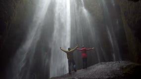 Молодые счастливые пары стоя под красивым водопадом Gljufrabui в Исландии и руках повышений, чувствуя свободе и утехе акции видеоматериалы