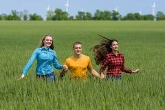 Молодые счастливые друзья бежать на зеленом пшеничном поле Стоковая Фотография
