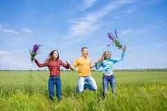 Молодые счастливые друзья бежать на зеленом пшеничном поле Стоковые Фотографии RF