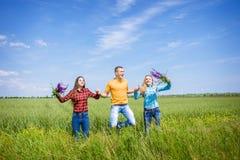 Молодые счастливые друзья бежать на зеленом пшеничном поле Стоковые Изображения