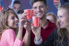 Молодые счастливые друзья во время партии Стоковое фото RF