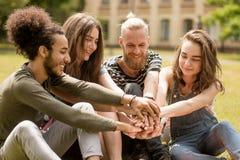Молодые счастливые студенты имея потеху, сидя в парке Стоковое Фото