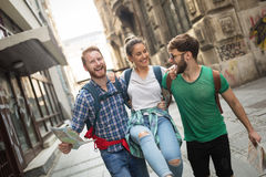 Молодые счастливые туристы sightseeing в городе стоковое фото
