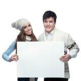 Молодые ся пары зимы держа большой знак Стоковые Фотографии RF